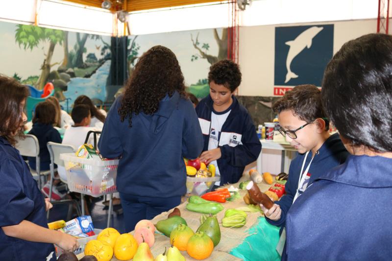 Alunos escolhendo suas compras no Mercado Escola.