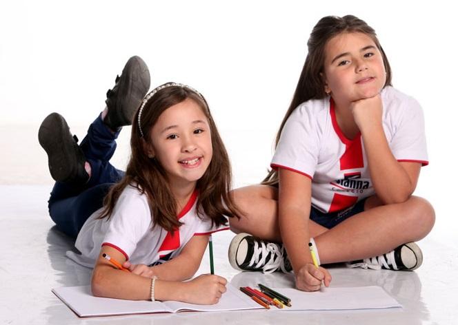 Uma estudante do Vianna deitada no chão escrevendo em seu caderno e outra estudante do Vianna sentada no chão escrevendo em seu caderno. Ambas olhando para a foto.