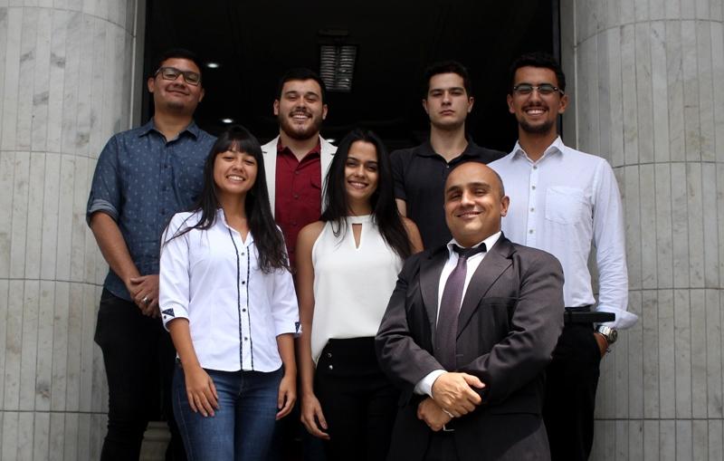 7 pessoas posando para foto na fachada do Vianna Júnior. 6 alunos, 4 homens e 2 meninas e 1 professor